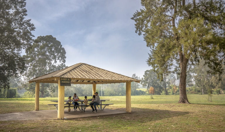 A family enjoying lunch in one of the picnic sheds at Cattai Farm picnic area, near Cattai campground in Cattai National Park. Photo: John Spencer/OEH