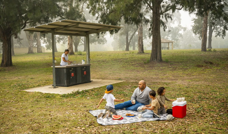 A man and his children sit on a picnic blanket while a woman cooks lunch on the barbecue, at Cattai Farm picnic area in Cattai National Park. Photo: John Spencer/OEH