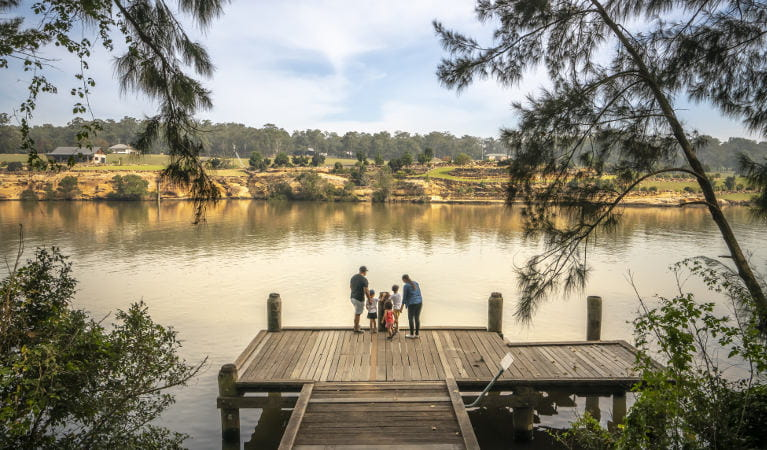 A family standing on a wooden jetty, looking across the Hawkesbury River, at Cattai Farm picnic area in Cattai National Park. Photo: John Spencer/OEH