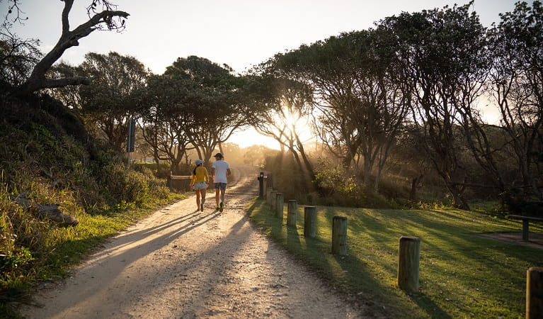 Walkers at sunset at Diamond Head campground, Crowdy Bay National Park. Photo: Rob Mulally/DPIE