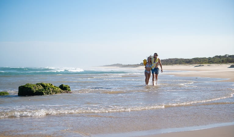 A couple enjoying the beach near Kylies Beach campground, Crowdy Bay National Park. Photo: Rob Mulally/DPIE