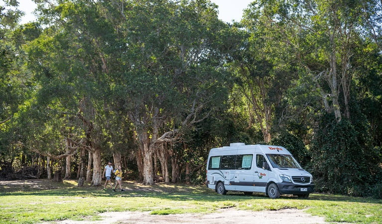 A couple walking across Kylies Beach campground to their campervan, Crowdy Bay National Park. Photo: Rob Mulally/DPIE