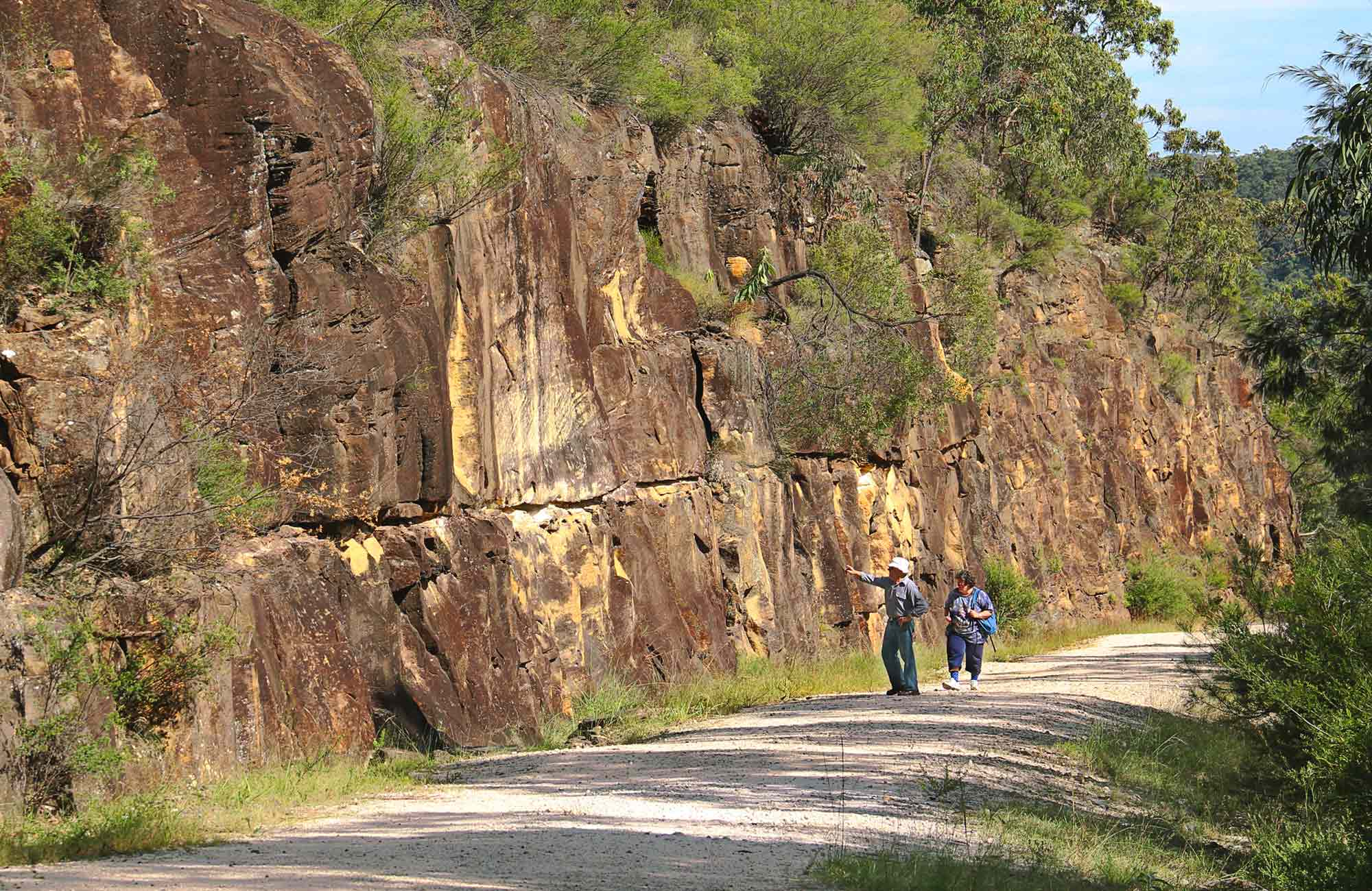 People walking along the track with high cliffs. Photo: John Yurasek