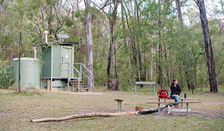 A visitor sits at a picnic table at Ten Mile Hollow campground in Dharug National Park. Photo: Nick Cubbin/DPIE