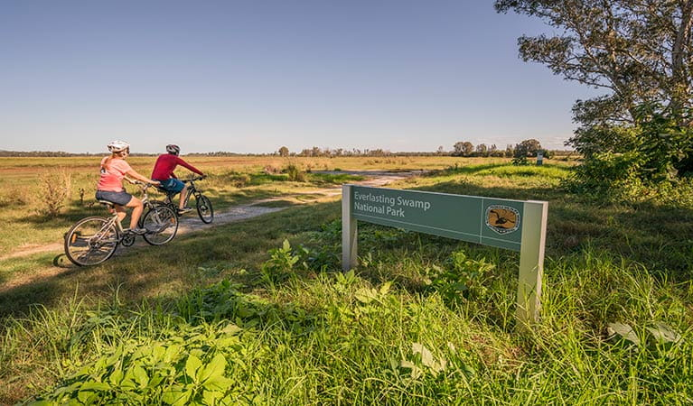 Cycling past the Everlasting Swamp National Park entrance sign. Photo: John Spencer/OEH
