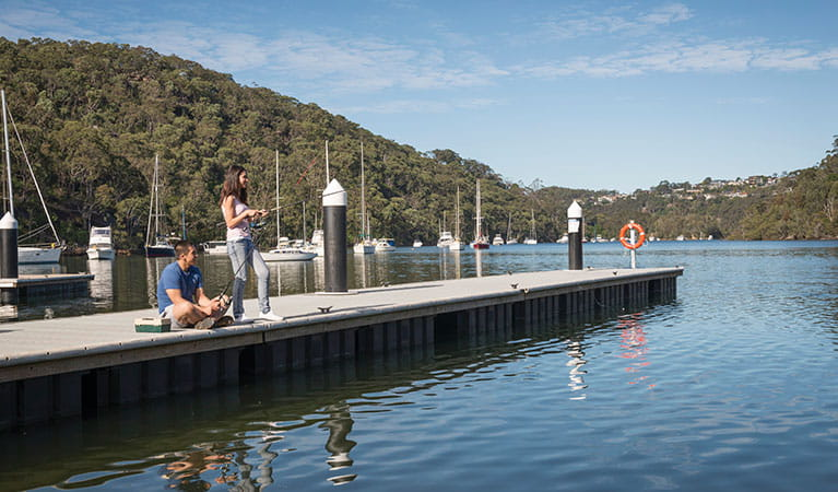 2 friends fishing on the wharf at Davidson Park picnic area in Garigal National Park. Photo: John Spencer/DPIE