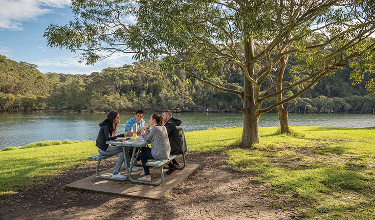 A group of friends at a picnic table next to Middle Harbour Creek in Davidson picnic area, Garigal National Park. Photo: John Spencer/DPIE