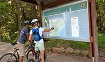 Cyclists looking at a park map. Photo: Shaun Sursok