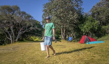 Camper with his fishing rod and bucket heading to the nearby beach, Goolawah National Park. Photo: John Spencer/OEH