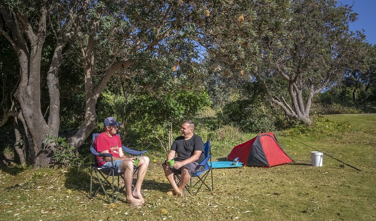2 campers sitting down beside their tent talking at Racecourse campground. Photo: John Spencer/OEH