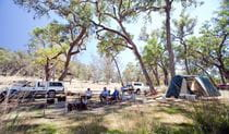 A group of people sitting beside their tent and car at Big River campground, Goulburn River National Park. Photo: Nick Cubbin © DPIE
