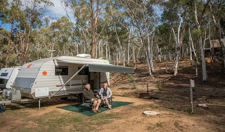 A couple sit outside their caravan in camping chairs, at Glendora campground in Hill End Historic Site. Photo: John Spencer/OEH
