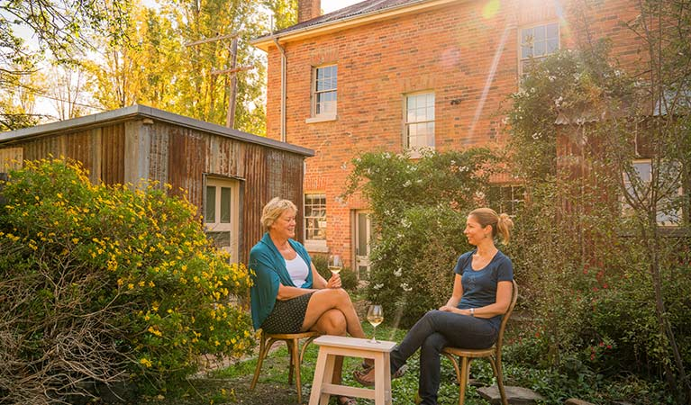Two women enjoy a drink in Hosies accommodation garden, Hill End Historic Site. Photo: J Spencer/OEH