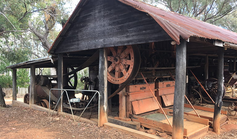 Rustic wood shed with metal roof containing historic farm machinery.  Photo: Brett Kearins/DPIE