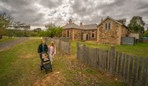 Family with baby walking past Post Office Residence in Hill End Historic Site. Photo: John Spencer/OEH