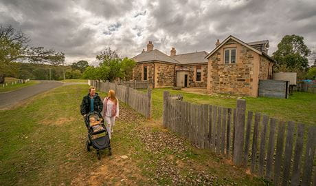Family with baby walking past Post Office Residence and Stables in Hill End Historic Site. Photo: John Spencer/OEH