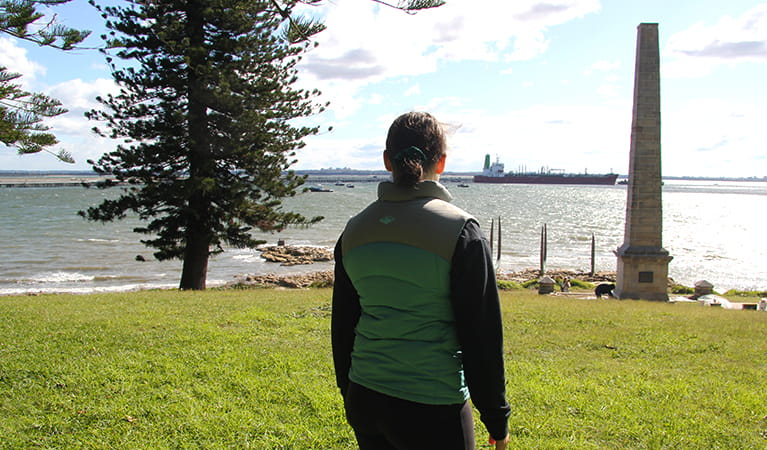 Girl looking out past Captain Cook Monument in Kurnell, Kamay Botany Bay National Park. Photo credit: Natasha Webb © DPIE