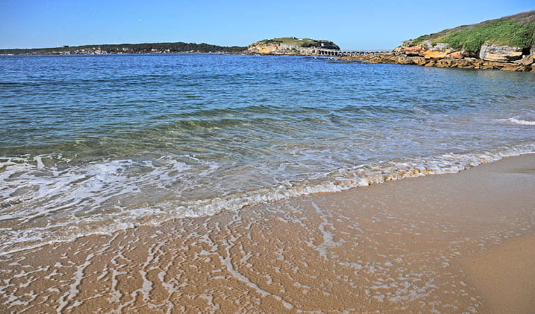 Gentle waves lap Congwong Beach, with Bare Island in background.  Photo: Kevin McGrath/OEH.