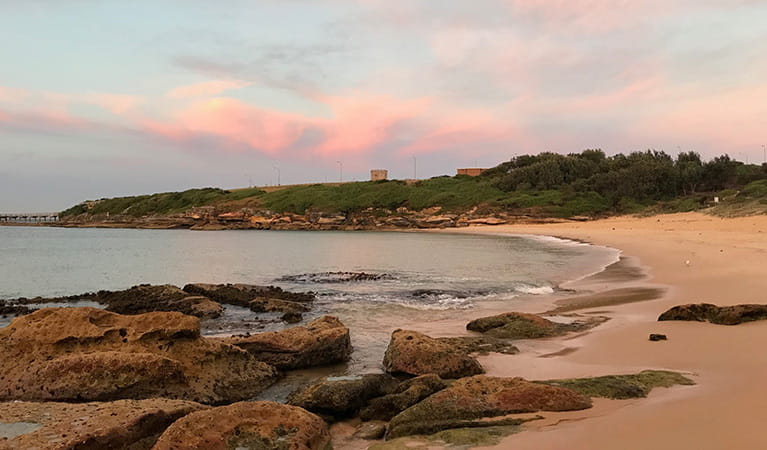 Congwong Beach at sunrise, with bushland and historic tower in the background. Photo: Stacy Wilson/OEH.