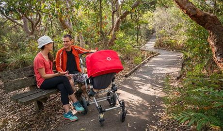 People sitting down on a timber bench with their pram in La Perouse area, Kamay Botany Bay National Park. Photo: J Spencer/OEH