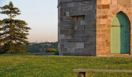 Detail of stone masonry and doorway of Macquarie watchtower, set on a grass lawn, with a pine tree in the background. Photo: Kevin McGrath/DPIE
