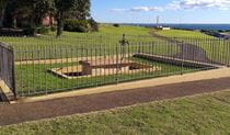 Fenced area with tomb and metal cross, on a wide grassy slope with Botany Bay in the background, near Sydney. Photo: Stacy Wilson/DPIE