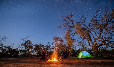 Campers stargazing by the fire at Emu Lake campground in Kinchega National Park. Photo: John Spencer/DPIE