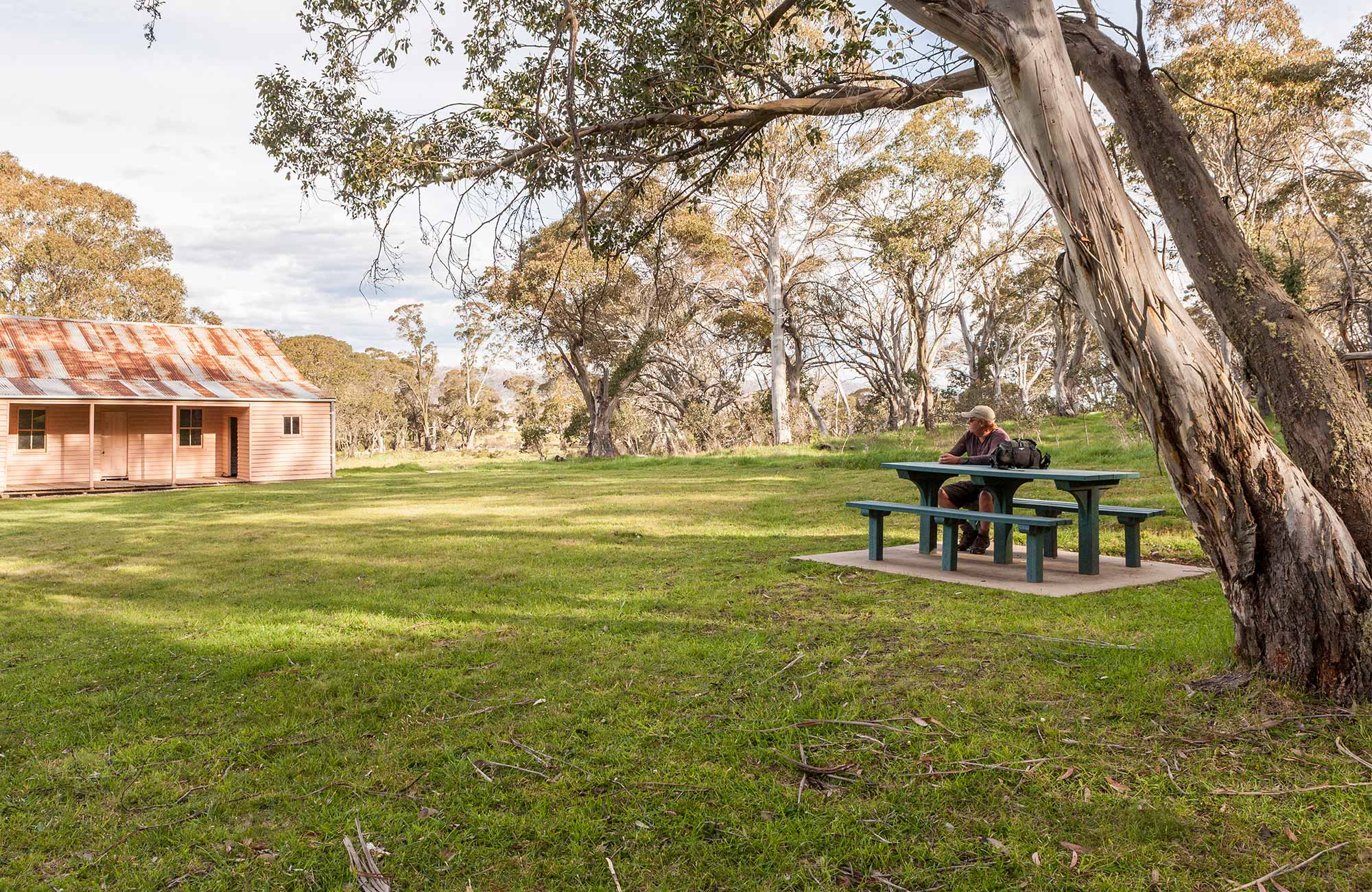 A man sits at a picnic table outside Long Plain Hut, High Plains area, Kosciuszko National Park. Photo: Murray Vanderveer