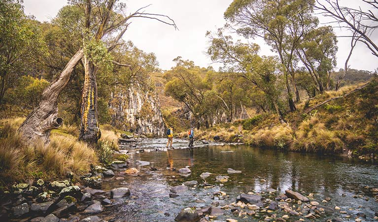Two men cross the river on Clarke Gorge walking track in northern Kosciuszko National Park. Photo: Robert Mulally/DPIE