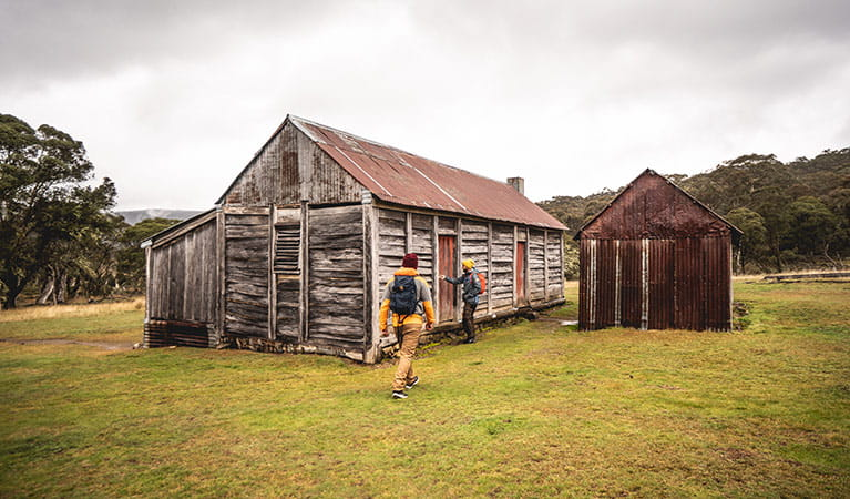 Two men outside a timber and tin building at Coolamine Homestead in Kosciuszko National Park. Photo: Robert Mulally/DPIE