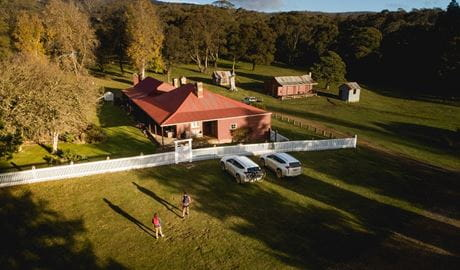 A bird's eye view of a couple walking towards Currango Homestead, Kosciuszko National Park. Photo: Rob Mulally/DPIE