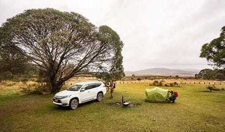 A man sets up a tent next to a fire ring and car at Long Plain Hut campground, Kosciuszko National Park. Photo: Robert Mulally/OEH