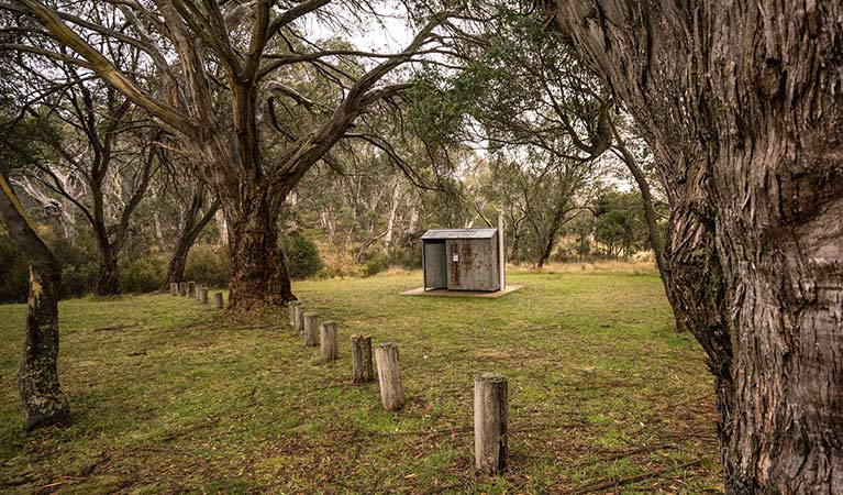 Non-flush toilet tin building among trees, Long Plain Hut campground, Kosciuszko National Park. Photo: Robert Mulally/OEH
