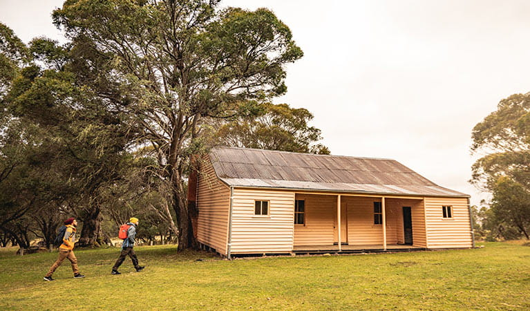 Two men walk towards Long Plain Hut in the High Plains area of Kosciuszko National Park. Photo: Robert Mulally/OEH