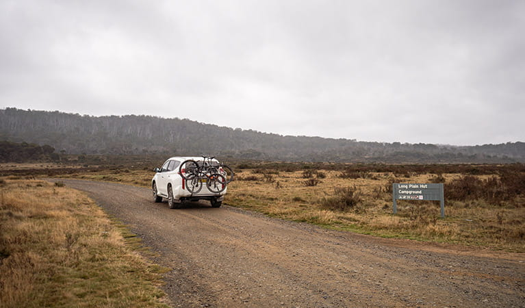 A car carrying bikes drives past a sign on an unsealed road, Kosciuszko National Park. Photo: Robert Mulally/OEH