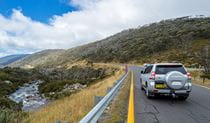 A 4WD vehicle drives towards Thredbo on Alpine Way, passing the Thredbo River near Dead horse Gap, Kosciuszko National Park. Photo: Murray Vanderveer/DPIE