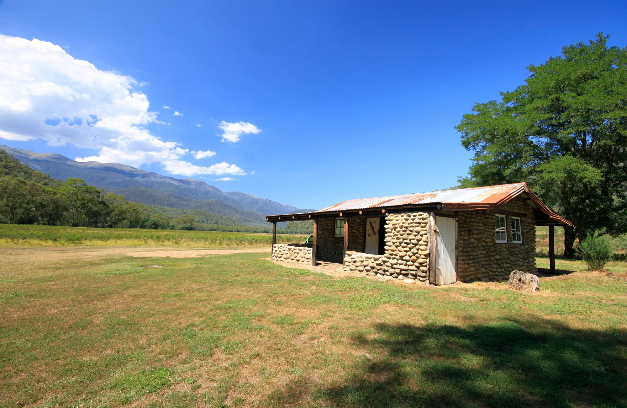 Historic hut on a grassy plain with mountains in the background. Photo: Elinor Sheargold/OEH.