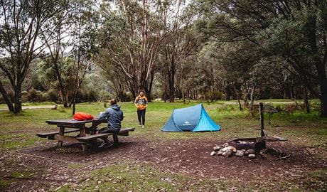 A man sits at a picnic table next to a tent at Geehi Flats campground, Kosciuszko National Park. Photo: Robert Mulally/OEH