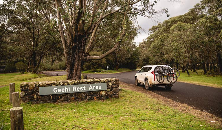 A car with bike rack passes a sign at Geehi Flats picnic area and campground, Kosciuszko National Park. Photo: Daniel Tran/OEH