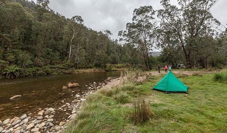 A green tent beside the Swampy Plain River at Old Geehi campground, Kosciuszko National Park. Photo: Murray Vanderveer/OEH