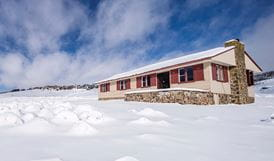 Exterior of Wolgal Hut surrounded by snow in winter, Kosciuszko National Park. Photo: Murray Vanderveer/OEH