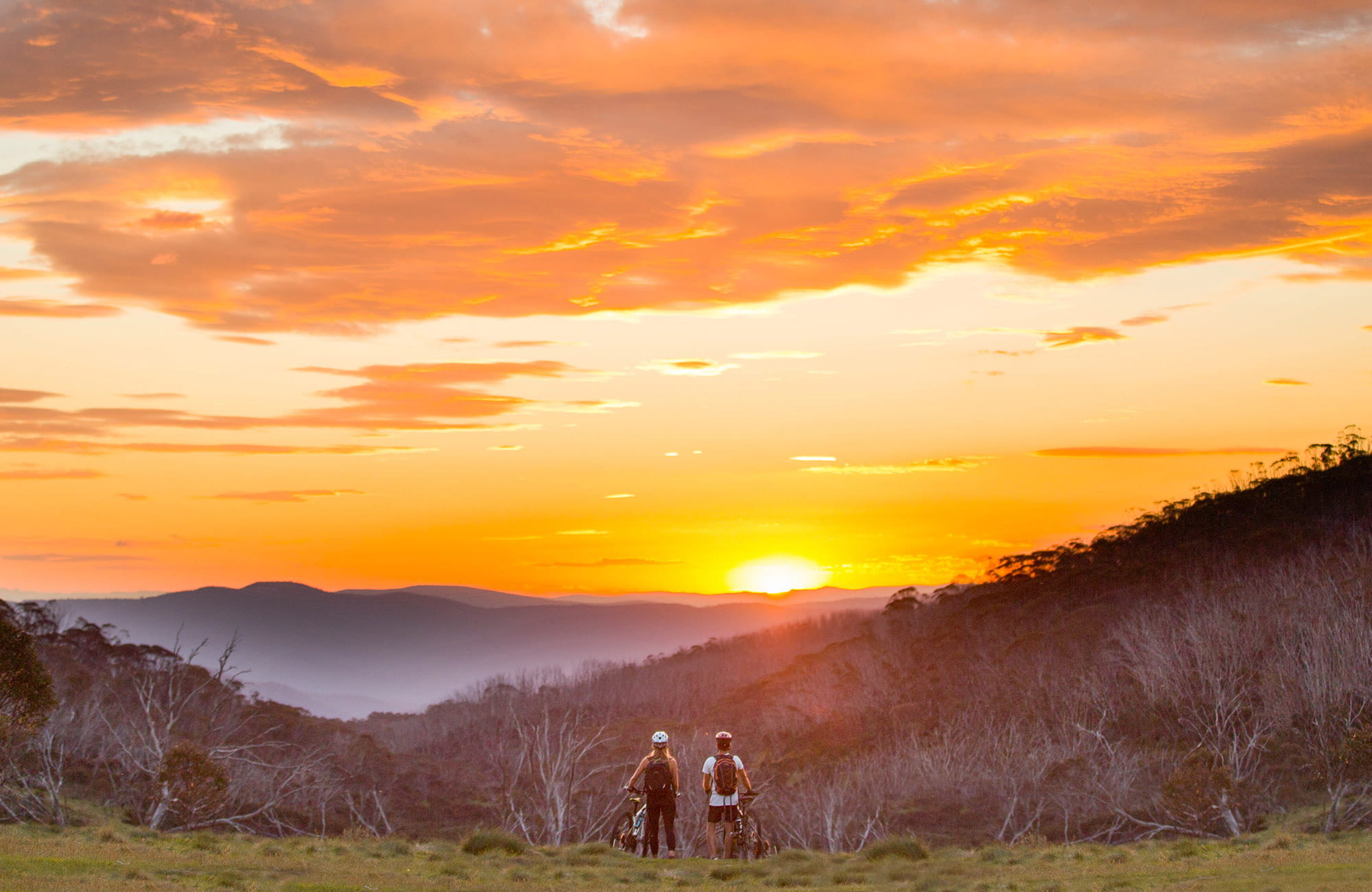 Two mountain bike riders enjoy the sunset from a hill near Thredbo village, in Kosciuszko National Park. Photo: Boen Ferguson/OEH.