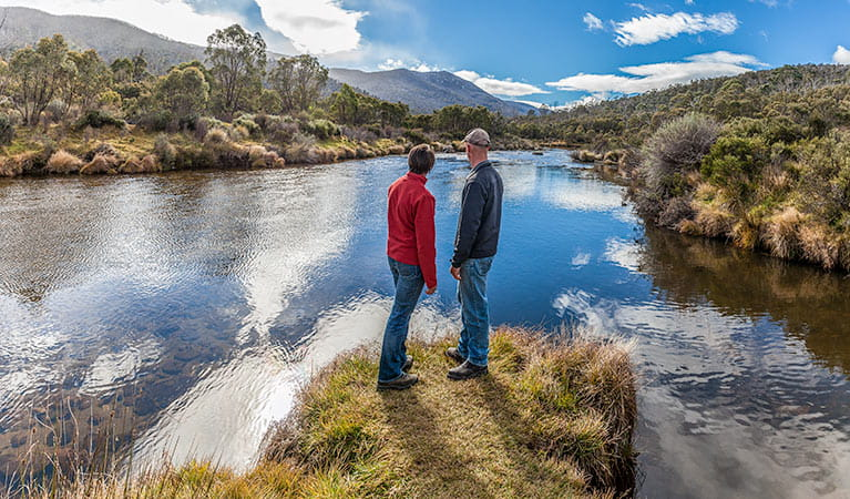 A man and woman stand beside the Thredbo River near Bullocks Hut, Kosciuszko National Park. Photo: Murray Vanderveer/DPIE