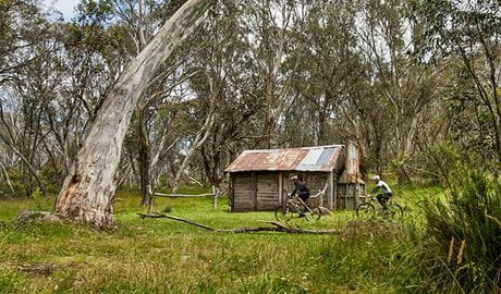 Two mountain bike riders cycle past Cascade Hut, in remote Kosciuszko National Park. Photo: Murray Vanderveer/DPIE