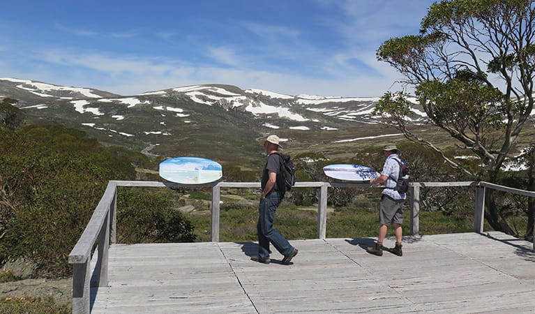 2 bushwalkers read park information at Charlotte Pass lookout, with mountains in the background. Photo: Elinor Sheargold/DPIE.