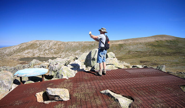 A man takes a photo at Cootapatamba lookout, with Mount Kosciuszko in the background, Kosciuszko National Park. Photo: Elinor Sheargold © DPIE