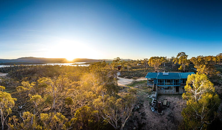 Aerial view of Creel Lodge, surrounded by bushland with Lake Jindabyne to the left and sunrise in the background. Photo: © Murray Vanderveer