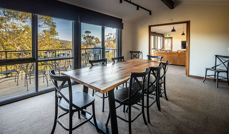 The spacious dining table at Creel Lodge with views of bushland and Lake Jindabyne through the window. Photo: © Murray Vanderveer