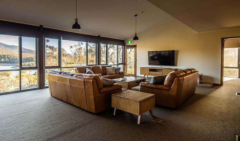 The spacious living area of Creel Lodge, with lounge set, TV and views of Lake Jindabyne through the window. Photo: © Murray Vanderveer