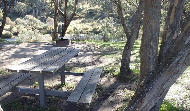 A timber picnic table at Gungarlin River, with a view of the river, Kosciuszko National Park. Photo: Andrew Miller/OEH